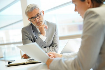Steuerberatung Poing Mann und Frau reden an Schreibtisch